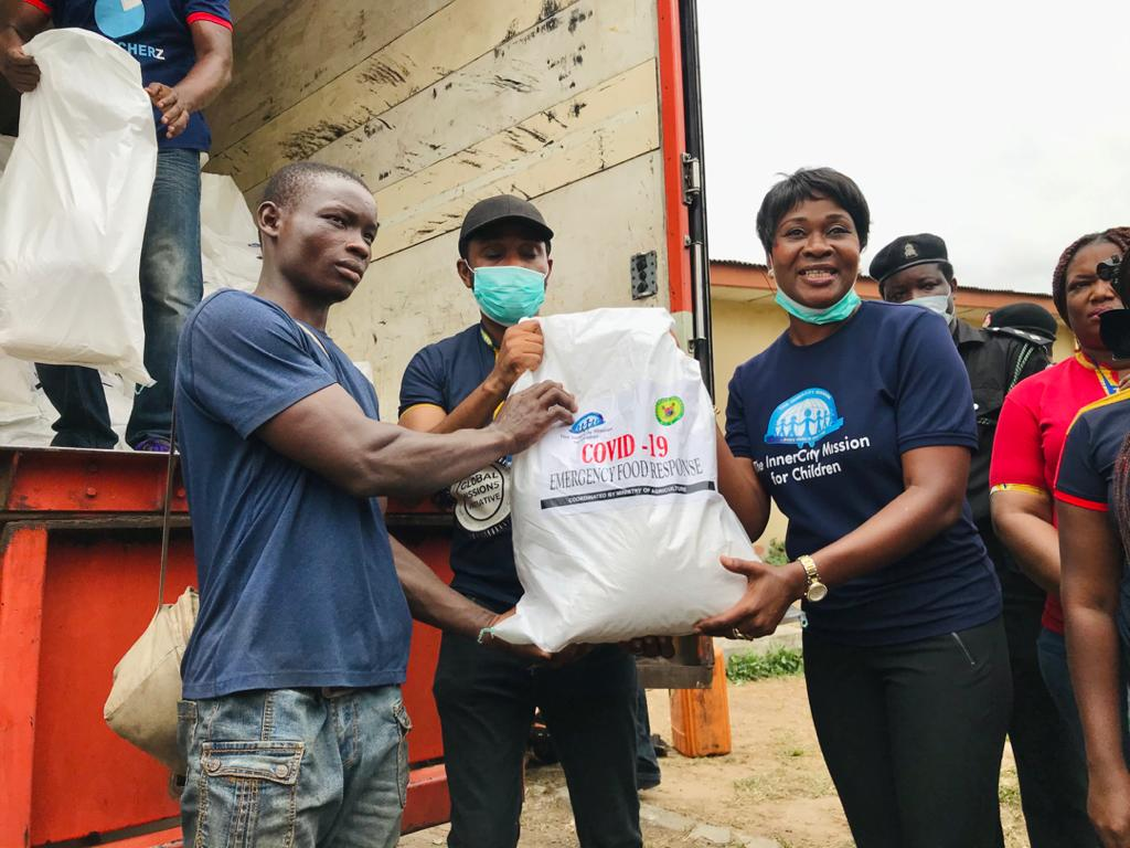 Director of Innercity Mission for Children, Mrs. Omo Alabi presenting food item to one of the beneficiaries